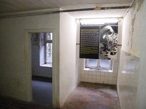 Nebenraum der ehemaligen Gaskammer in der heutigen KZ Gedenkstätte Mauthausen samt Informationstafel zur Gaskammer - Bildquelle: Wikipedia, public domain.